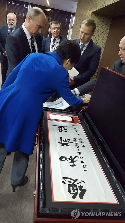 This photo, taken on Sept. 3, 2016, and provided by the presidential office Cheong Wa Dae, shows President Park Geun-hye looking at the calligraphy of her late father and former President Park Chung-hee after a working luncheon at the Eastern Economic Forum in Russia's Far East port city of Vladivostok. (Yonhap)