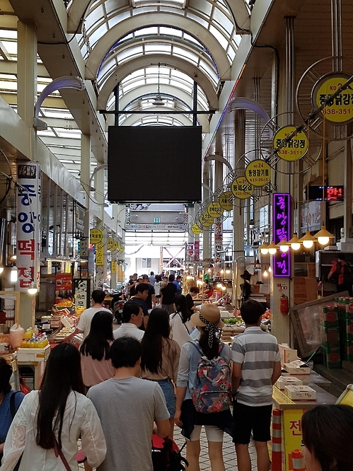 "In the photo, taken on July 18, 2016, many tourists and shoppers bustle around one of two major alleys at Sokcho Tourist Fish Market in South Korea's eastern Gangwon Province. The alley, known as ""chicken and cake alley,"" is home to nearly dozen shops that specialize in nationwide famous sweet and sour chicken. (Yonhap)"