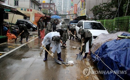 This photo, taken on Oct. 8, 2016, shows soldiers removing road debris in a marketplace in Ulsan, a southern city affected by Typhoon Chaba. (Yonhap)