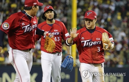 Kia Tigers' shortstop Kim Sun-bin (R) high-fives second baseman An Chi-hong after the two turned a double play against the LG Twins during the Korea Baseball Organization's wild card game in Seoul on Oct. 10, 2016. (Yonhap)