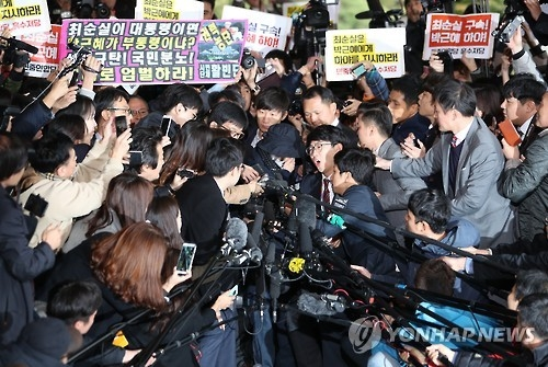 Choi Soon-sil, who is suspected of having meddled in state affairs and peddling influence on various state projects by exploiting her decades-long friendship with President Park Geun-hye, passes through a huge group of reporters to enter the Seoul Central District Prosecutors' Office in Seoul for questioning on Oct. 31, 2016. (Yonhap)
