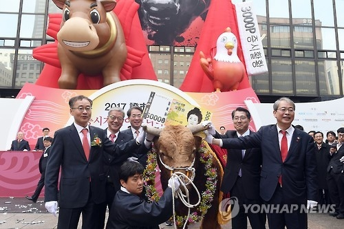 Yim Jong-yong (R), chairman of the Financial Services Commission, poses for a photo with a bull during a ceremony to mark the opening of this year's stock trading at the Seoul bourse on Jan. 2, 2017. (Yonhap)