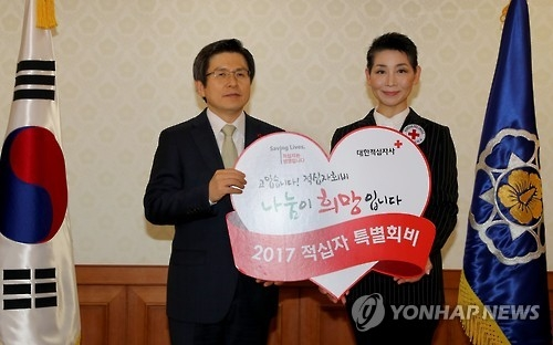 Acting President and Prime Minister Hwang Kyo-ahn (L) and South Korea's Red Cross chief Kim Sung-joo pose for a photo after Hwang made his monetary donations to the organization at the central government complex in Seoul on Jan. 6, 2017. (Yonhap)