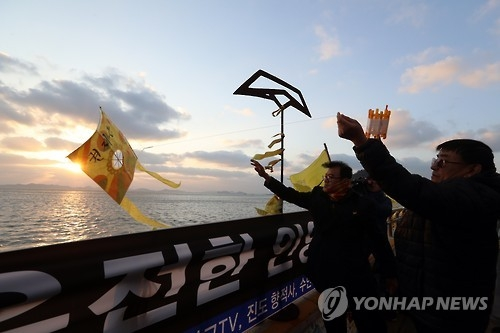 A family member of a victim flies a kite at Paengmok Harbor on Jan. 9, 2017, wishing for his brother's return on the 1,000th day since the ferry Sewol sank. (Yonhap)