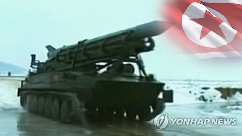 This undated captured image from Yonhap News TV shows a missile mounted on mobile launcher against the flag of North Korea. (Yonhap)