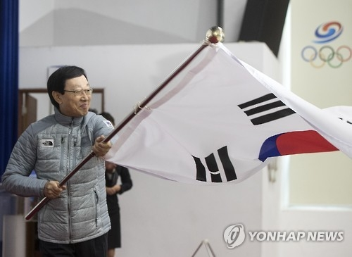 Kim Sang-hang, head of the South Korean delegation to the Sapporo Asian Winter Games, waves the national flag during the team launch ceremony at the National Training Center in Seoul on Feb. 3, 2017. (Yonhap)
