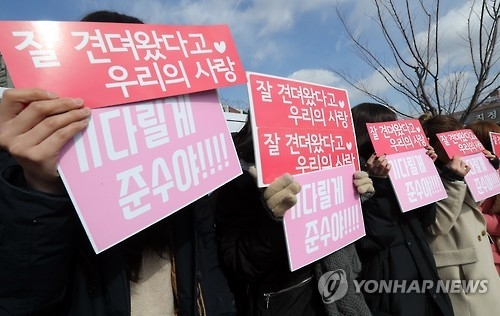 Fans hold signs for Kim Jun-su from K-pop idol group JYJ who is began his military service in Nonsan, South Chungcheong Province, on Feb. 9, 2017. (Yonhap)