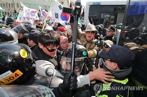 Protesters from conservative civic bodies scuffle with police at an intersection leading to the Constitutional Court in Seoul on March 10, 2017, after the court upheld the impeachment of the president. The ruling, which was announced by the court's acting chief and televised live, made Park the nation's first democratically elected leader to be ousted. (Yonhap)