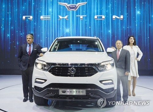 In this photo, taken on March 30, 2017, Mahindra & Mahindra Ltd. Executive Chairman Anand Mahindra (L) and its South Korean unit SsangYong Motor Co. CEO Choi Johng-sik (R) pose with SsangYong's new G4 Rexton SUV during the Seoul Motor Show press day held at KINTEX exhibition hall near Seoul. (Yonhap)