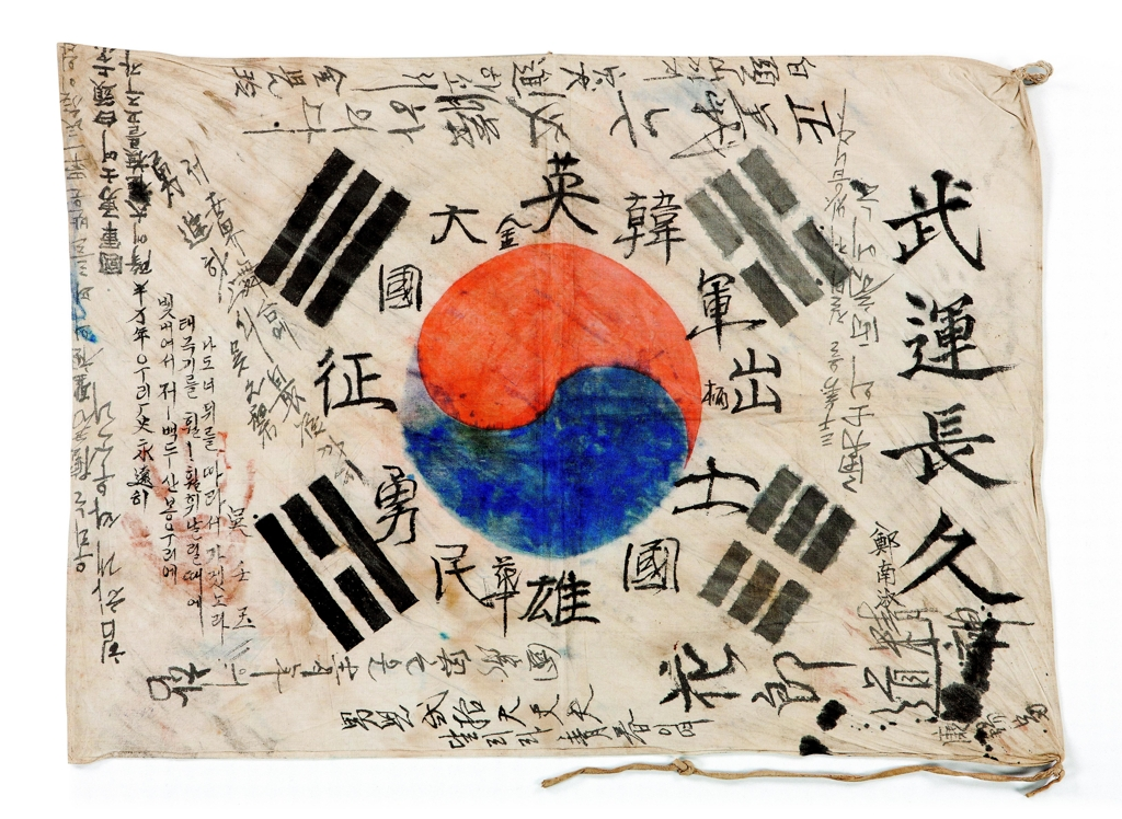 The photo provided by the National Museum of Korean Contemporary History shows the Korean national flag Taegukgi on which soldiers wrote down messages wishing for victory. (Yonhap)