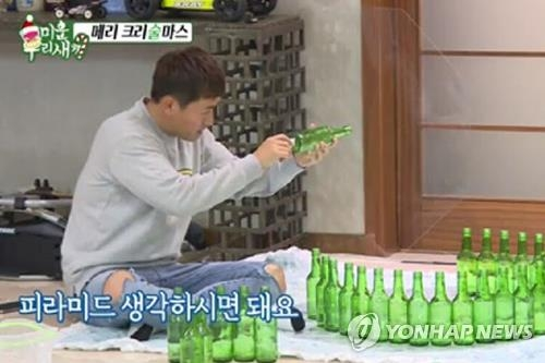 "This image captured from SBS TV's reality television show ""Mom's Diary -- My Ugly Duckling"" shows singer Kim Gun-mo building a Christmas tree out of empty soju bottles. (Yonhap)"