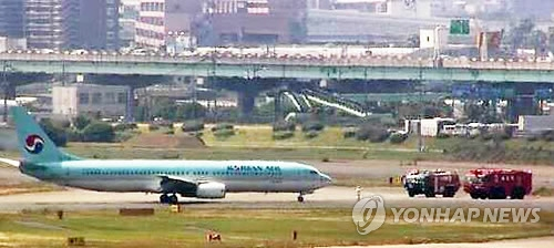 This captured image from Japan's largest broadcaster NHK shows fire trucks and Korean Air Line's B737-900 jet at Fukuoka airport after smoke was detected in the cockpit five minutes before landing on June 9, 2017. (Yonhap)