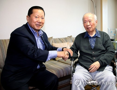 In this file photo provided by the Korean Olympic Committee (KOC) on Feb. 3, 2016, Kim Jung-haeng (L), head of the KOC at the time, shakes hands with Suh Yun-bok, the 1947 Boston Marathon champion. Suh passed away on June 27, 2017, at age 94. (Yonhap)