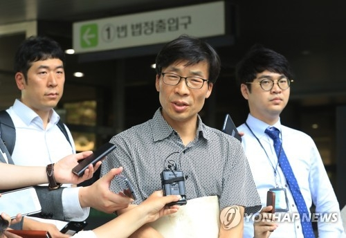 Kang Ki-hoon (C) speaks to reporters outside the courthouse in Seoul, on July 6, 2017, about his compensation suit against the state over the false accusations brought against him in the 1990s. (Yonhap)
