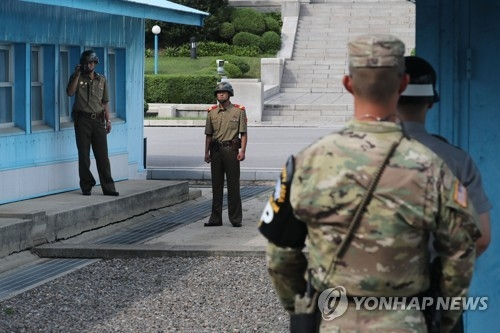 South and North Korean soldiers face off with each other at the truce village of Panmunjom in this file photo. (Yonhap)