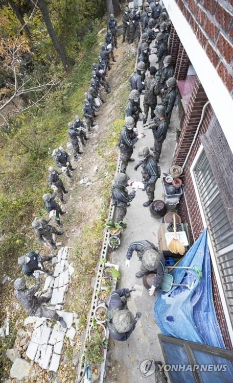 A group of Army soldiers clears the debris of a collapsed wall at a house in the southeastern city of Pohang on Nov. 17, 2017, which was hit by a magnitude 5.4 quake on Nov. 15. (Yonhap)