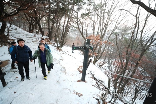 President Moon Jae-in (R) climbs Mount Bukhan on New Year's Day, 2018. (Yonhap)