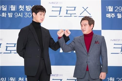 "Actor Go Kyung-pyo (L) poses with actor Cho Jae-hyun for photos at a press briefing for the new TV series ""Cross"" on tvN in Seoul on Jan. 25, 2018. (Yonhap)"