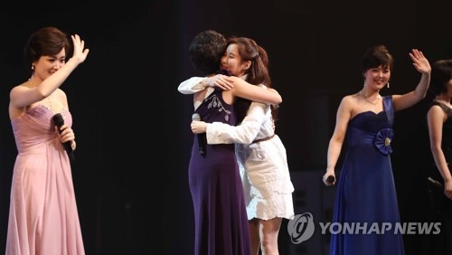 Seohyun, a member of South Korean pop group Girls' Generation, hugs a North Korean singer during the Samjiyon Orchestra's performance in Seoul on Feb. 11, 2018. (Yonhap)