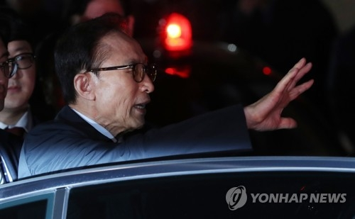 Former President Lee Myung-bak waves to his aides before getting in a sedan in front of his home in Seoul on March 23, 2018, after a court issued an arrest warrant for him on bribery, embezzlement, tax evasion and other charges. He was taken to the Seoul Eastern Detention Center, becoming the nation's fourth former president to be arrested for corruption. (Yonhap)