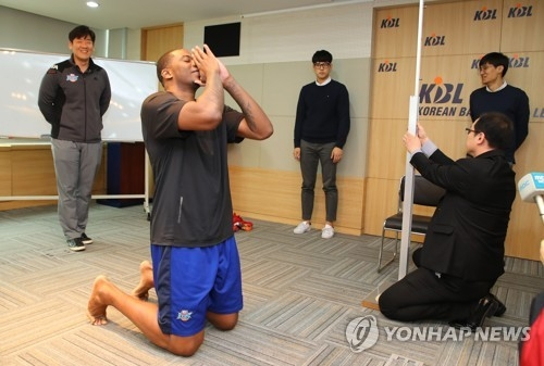 In this file photo taken April 6, 2018, Jeonju KCC Egis player Charles Rhodes (2nd from L) celebrates after he passed the Korean Basketball League's height limit of 200 centimeters after having his height measured at the KBL Center in Seoul. (Yonhap)