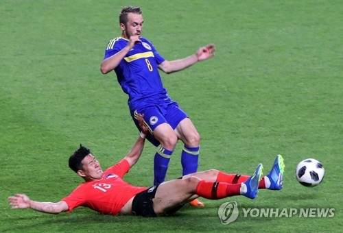Son Heung-min of South Korea (L) tackles Edin Visca of Bosnia and Herzegovina in a World Cup tune-up match at Jeonju World Cup Stadium in Jeonju, 240 kilometers south of Seoul, on June 1, 2018. (Yonhap)