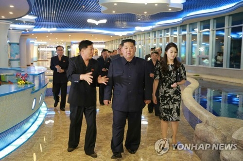 A June 9, 2018, photo from the Rodong Sinmun shows North Korean leader Kim Jong-un (C) and his wife Ri Sol-ju visiting a new seafood restaurant in Pyongyang. (For Use Only in the Republic of Korea. No Redistribution) (Yonhap)
