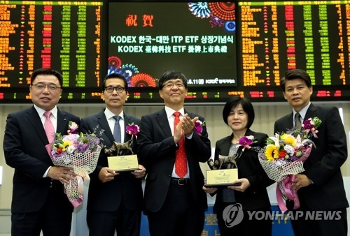 Officials from South Korea and Taiwan pose for a picture during an event held in Seoul on June 11, 2018, to list the KODEX Korea Taiwan IT Premier ETF on the South Korean bourse.