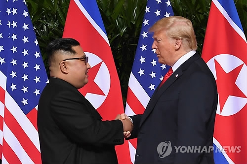 U.S. President Donald Trump (R) and North Korean leader Kim Jong-un shake hands at the Capella Hotel on Sentosa Island in Singapore on June 12, 2018, ahead of their first historic summit. (Yonhap)