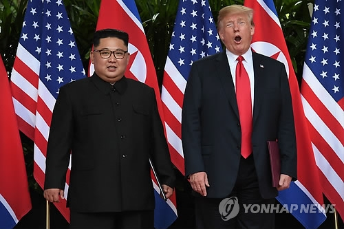 U.S. President Donald Trump and North Korean leader Kim Jong-un pose for a photo after signing their summit agreement in Singapore on June 12, 2018, in this photo released by the AFP. (Yonhap)