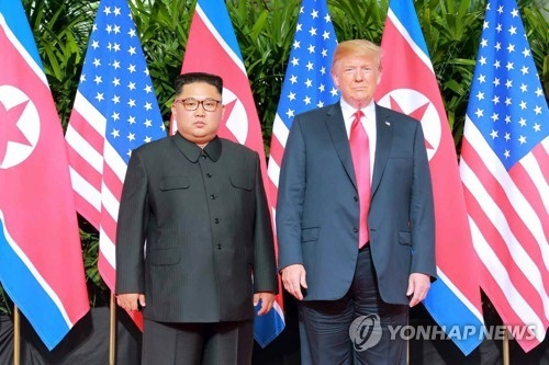 This photo, taken from the North's Rodong Sinmun daily newspaper on June 13, 2018, shows North Korean leader Kim Jong-un (L) posing with U.S. President Donald Trump before a row of their national flags ahead of a summit on Singapore's resort island of Sentosa a day earlier. (For Use Only in the Republic of Korea. No Redistribution) (Yonhap)