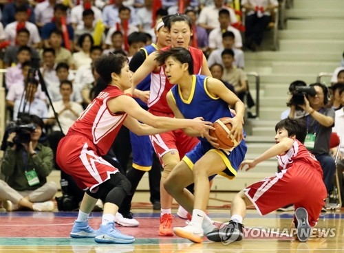 In this Joint Press Corps photo, South Korean player Park Ji-hyun (with ball, in blue) tries to fend off North Korean defenders during a friendly basketball game against North Korea at Ryugyong Chung Ju-yung Gymnasium in Pyongyang on July 5, 2018. (Yonhap)