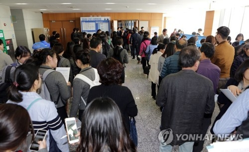 Jobseekers wait in line at a job fair organized by a district office in Seoul on March 29, 2018, in this file photo. (Yonhap)