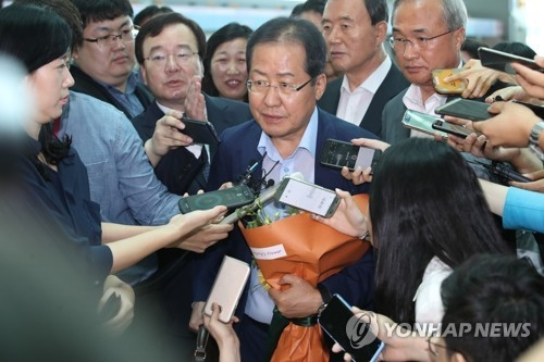 This photo taken on July 11, 2018, shows Hong Joon-pyo, the former chief of the main opposition Liberty Korea Party, surrounded by reporters at Incheon International Airport before leaving for the United States following the party's defeat in the June local elections. (Yonhap)