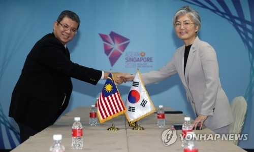 South Korean Foreign Minister Kang Kyung-wha (R) shakes hands with her Malaysian counterpart Saifuddin Abdullah in a Singapore meeting on Aug. 1, 2018. (Yonhap)