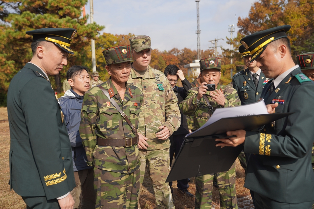 This photo, provided by South Korea's defense ministry, shows military officials from the two Koreas and the U.N. Command carrying out joint work to verify the disarmament of the Joint Security Area inside the Demilitarized Zone. (Yonhap)