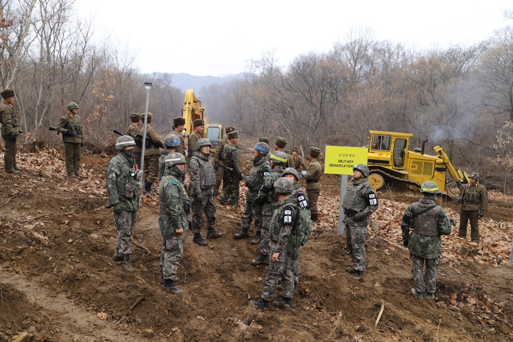 This photo, provided by South Korea's defense ministry, shows South and North Korean troops during a recent operation near the Military Demarcation Line to construct a tactical road to support a joint project to excavate Korean War remains in the Demilitarized Zone. (Yonhap)