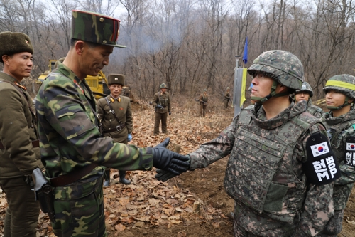 This photo, provided by South Korea's defense ministry, shows a South Korean official shaking hands with his North Korean counterpart during a recent operation near the Military Demarcation Line to construct a tactical road to support a joint project to excavate Korean War remains in the Demilitarized Zone. (Yonhap)