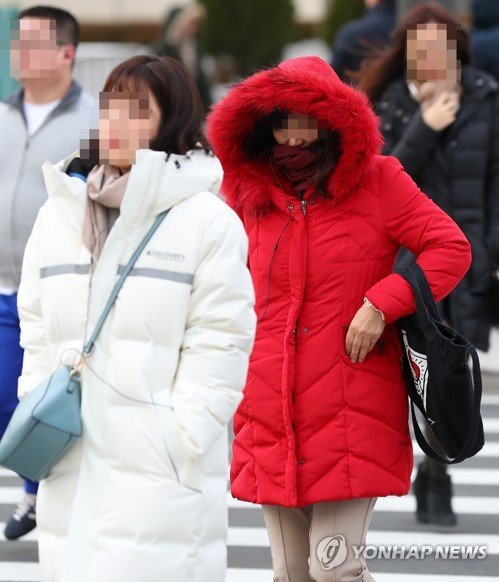 Citizens, clad in thick winter clothes, cross a street in central Seoul on their way to work on Dec. 5, 2018, as the morning low drops well below zero in the South Korean capital. (Yonhap)