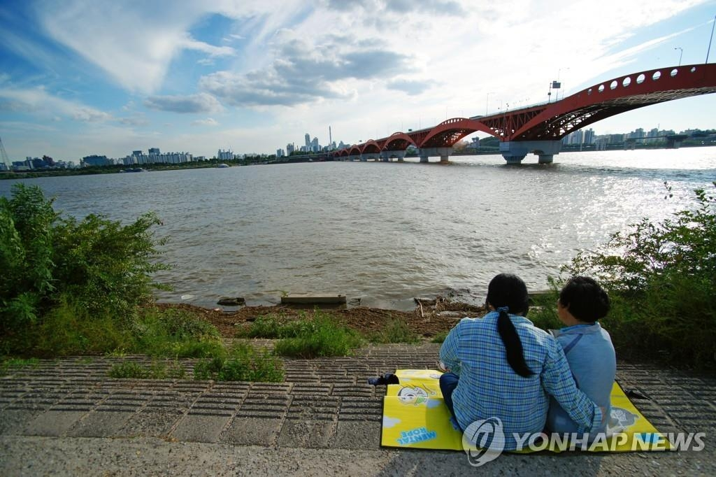 People enjoy leisure time by the Han River at a spot with a view of the Seongsan Bridge on Aug. 7, 2018. (Yonhap)
