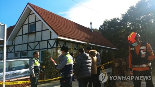 Firefighters and police investigators gather at a pension in the city of Gangneung on South Korea's east coast on Dec. 18, 2018, where yellow police tape surrounds the scene where three students were found dead and seven others unconscious. (Yonhap)