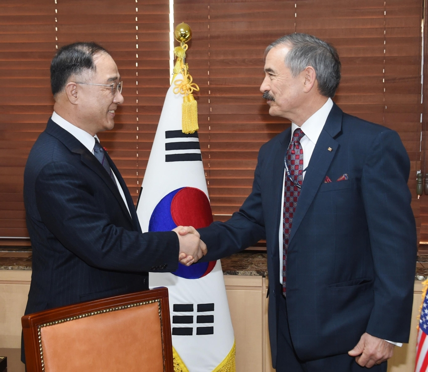 Hong Nam-ki (L), the minister of economy and finance, shakes hands with U.S. Ambassador to South Korea Harry Harris ahead of their talks at the government complex building across from the U.S. Embassy in central Seoul on Jan. 11, 2019. This photo was provided by the Ministry of Economy and Finance. (Yonhap)