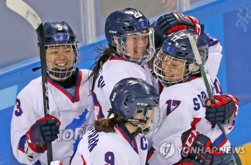 Members of the joint women's ice hockey team of the two Koreas congratulate each other in their match with Sweden at Kwandong Hockey Centre in Gangneung, around 240 kilometers east of Seoul, on Feb. 20, 2018. (Yonhap)