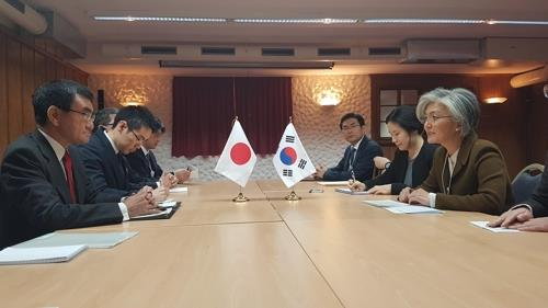 South Korean Foreign Minister Kang Kyung-wha (R) speaks with her Japanese counterpart Taro Kono during their talks at a hotel in Davos, Switzerland, on Jan. 23, 2019. (Yonhap)