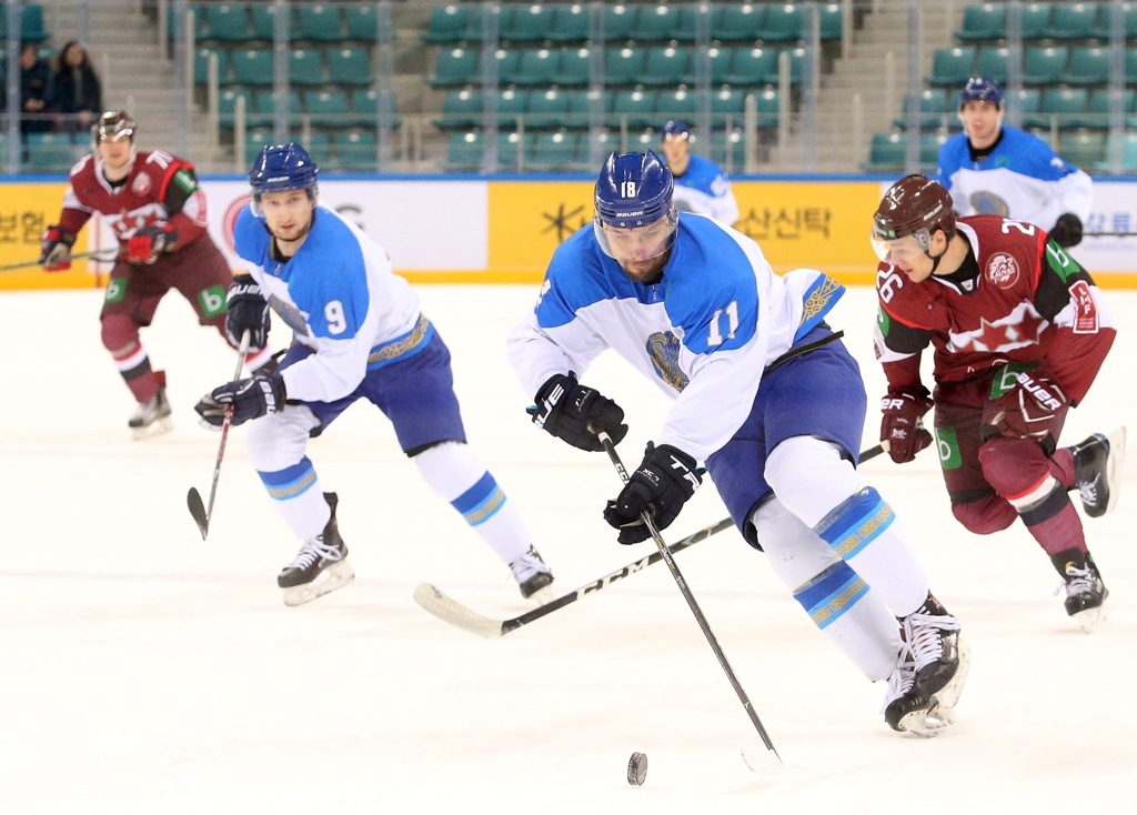 In this photo provided by the Korea Ice Hockey Association, Artem Likhotnikov of Kazakhstan (2nd from R) controls the puck against Latvia in the teams' final match at the Legacy Cup men's hockey tournament at Gangneung Hockey Centre in Gangneung, 230 kilometers east of Seoul, on Feb. 8, 2019. (Yonhap)
