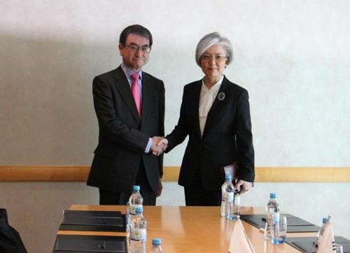 South Korean Foreign Minister Kang Kyung-wha (R) and her Japanese counterpart, Taro Kono, shake hands before holding bilateral talks in Berlin on Feb. 15, 2019. (Yonhap)