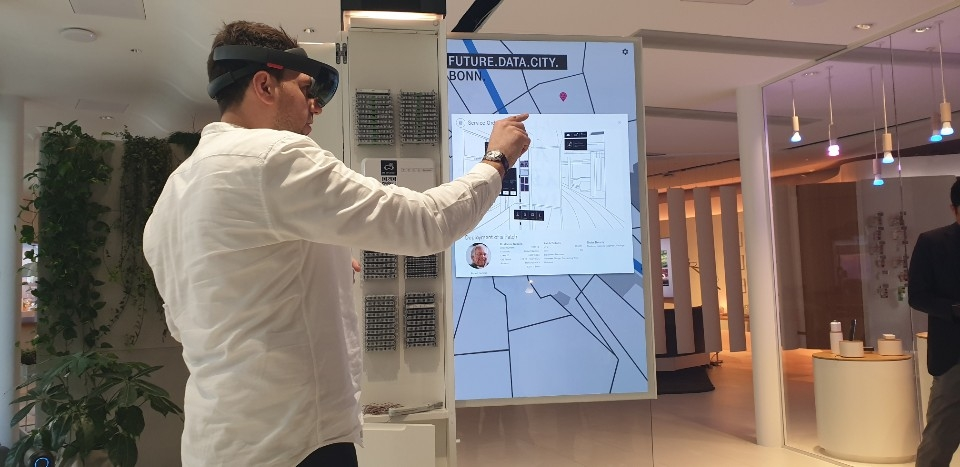 A demonstrator wearing augmented reality glasses checks a digital map at the Telekom Design Gallery at Deutsche Telekom's headquarters in Bonn on Feb. 28, 2019. (Yonhap)