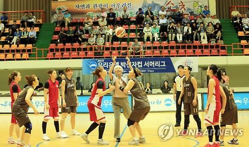 In this file photo from July 6, 2015, Park Shin-ja (C), a former South Korean women's basketball player, throws the ball for the ceremonial tipoff at the start of the Park Shin-ja Cup Summer League in Sokcho, 210 kilometers east of Seoul. (Yonhap)