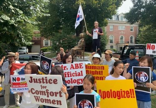 Activists rally outside the Japanese Embassy in Washington on Aug. 15, 2019. In the background is a statue of a girl symbolizing Korean women who were forced into sexual slavery by Japan during World War II. (Yonhap)