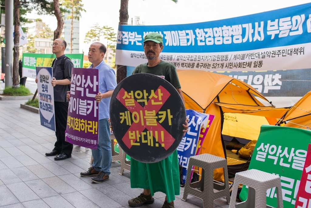 Environmental activist Park Grimm leads a sit-in protest across from Seoul Station on Aug. 14, 2019, to demand the cancellation of the planned Mount Seorak cable car. (Yonhap)